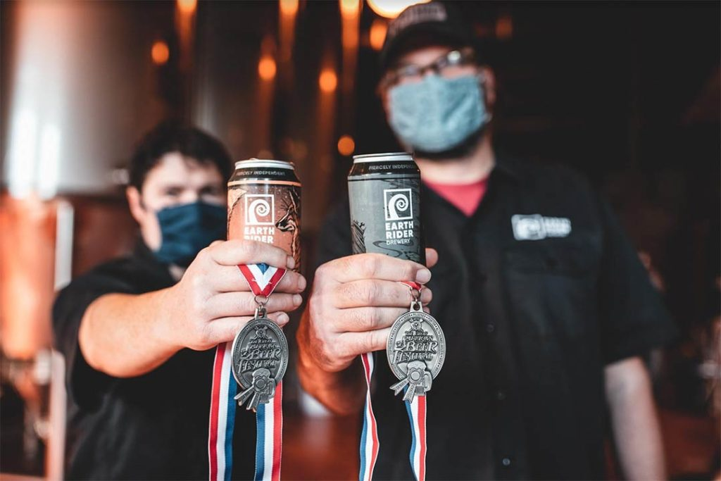 Brewers holding award winning Earth Rider beers